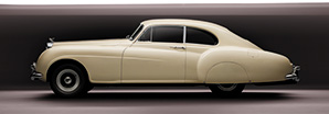 A side profile shot of a pearl white iconic Bentley R-Type Continental | Bentley Motors