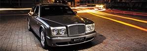 The powerful Bentley Arnage T in silver parked on a busy city road | Bentley Motors