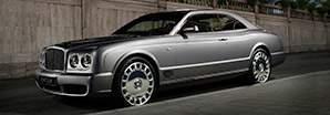 The silver Bentley Brooklands parked outside a luxury beach resort | Bentley Motors