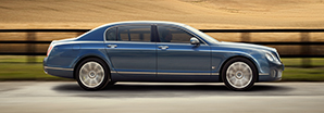A blue Bentley Continental Flying Spur Series 51 driving on a country road | Bentley Motors