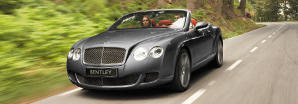 A dark grey Bentley Continental GT Speed Convertible driving on a country road | Bentley Motors
