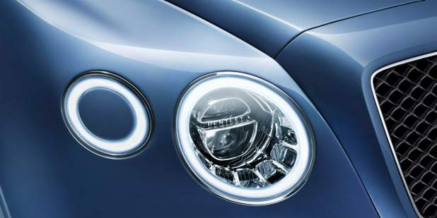 The main headlamp of a blue Bentley Bentayga Diesel SUV | Bentley Motors