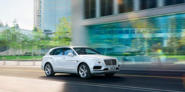 Bentayga Hybrid driving by a modern building with blue and green reflections, with trees and buildings in the background