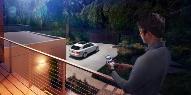 Man activating functionality on Bentayga Hybrid using his phone outside a modern luxury house