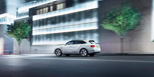 Bentayga Hybrid in white colour driving past lit building and trees in city 1398x699.jpg
