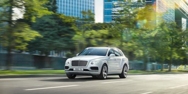 bentayga-speed-driving-on-city-road-past-trees-1398x699.jpg