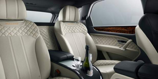 Rear seats with car bottle cooler insider the Bentley Bentayga Mulliner | Bentley Motors