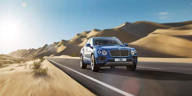 Blue Bentley Bentayga driving on the road surrounded by sand dunes | Bentley Motors