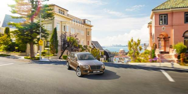 Bronze Bentayga turning a corner with a view overlooking houses and a city | Bentley Motors