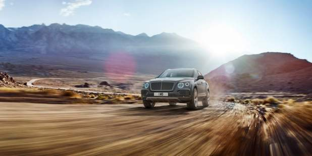 Grey Bentayga driving off road with the sun peeking through the mountain view | Bentley Motors