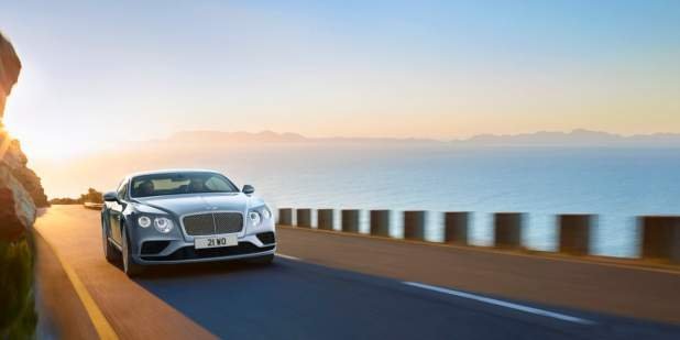 Light blue Bentley Continental GT driving on a hill side overlooking the sea | Bentley Motors