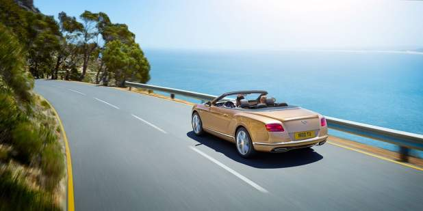 Bentley Continental GT Convertible driving along a cliff side road overlooking the sea | Bentley Motors