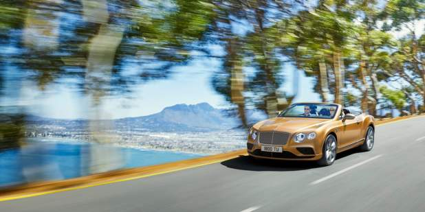 Bronze Bentley Continental GT Convertible driving on a road with a sea view | Bentley Motors