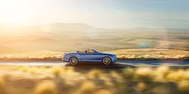 Blue Continental GT Speed Convertible driving along a country road surrounded by fields | Bentley Motors