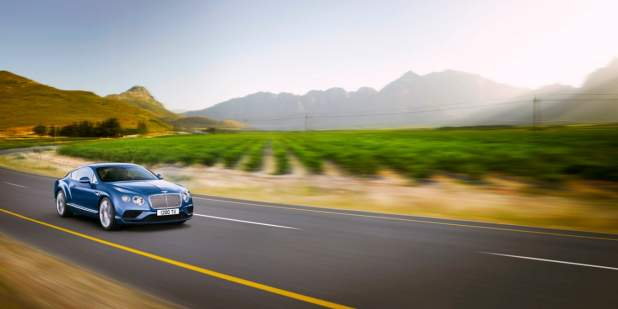 Blue Bentley Continental GT V8 on a country road with a mountain view | Bentley Motors