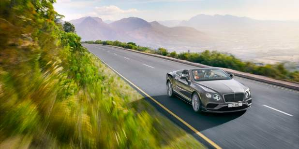 Dark grey Bentley Continental GT V8 S Convertible driving on a country road | Bentley Motors