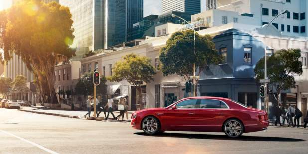 Red Bentley Flying Spur V8 S driving past shops and buildings | Bentley Motors