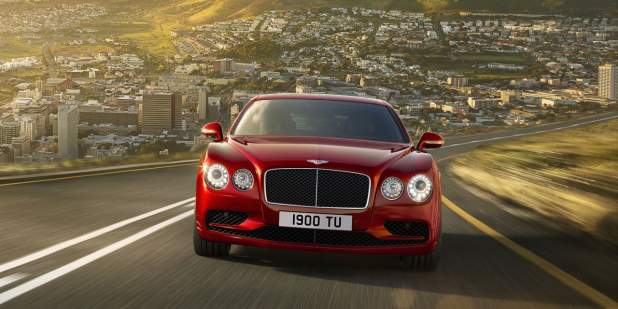 Red Bentley Flying Spur V8 S driving with a city in the background | Bentley Motors