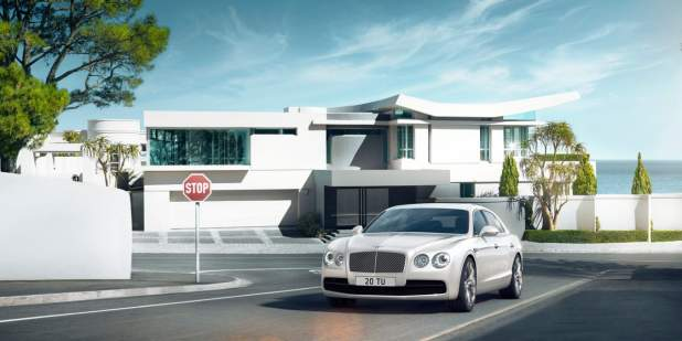 White Bentley Flying Spur V8 parked in front of a modern apartment | Bentley Motors