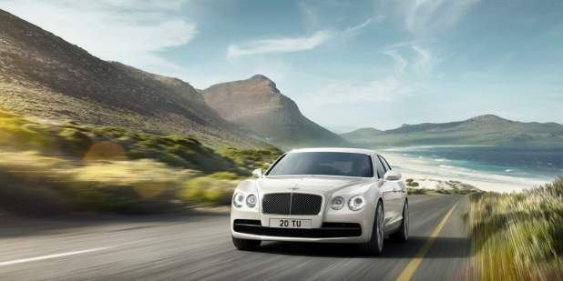 White Bentley Flying Spur driving away from the ocean on a country road | Bentley Motors