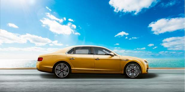 Side view of a gold Bentley Flying Spur V8 on a coastal road | Bentley Motors