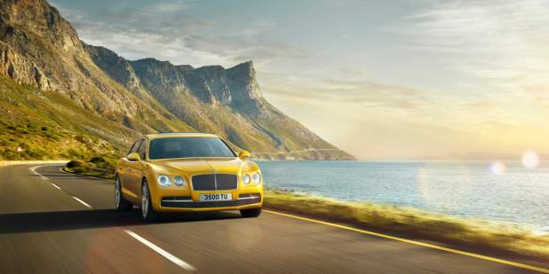 Front view of a gold Bentley Flying Spur driving on a coastal road | Bentley Motors