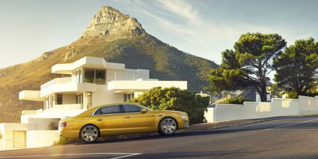 Gold Bentley Flying Spur parked in front of a house with mountain view | Bentley Motors