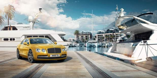 Gold Bentley Flying Spur parked in a harbour surrounded by yachts | Bentley Motors