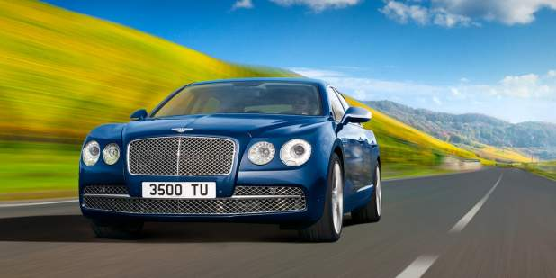 Blue Bentley Flying Spur W12 driving on a country road | Bentley Motors