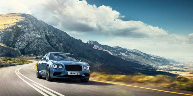 Blue Bentley Flying Spur W12 S driving on a country road | Bentley Motors