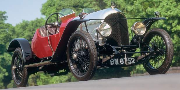 A red Bentley 3-Litre from the 1920s parked on a racing course | Bentley Motors