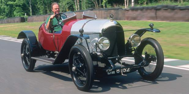 A red Bentley 3-Litre from the 1920s being driven outdoors | Bentley Motors