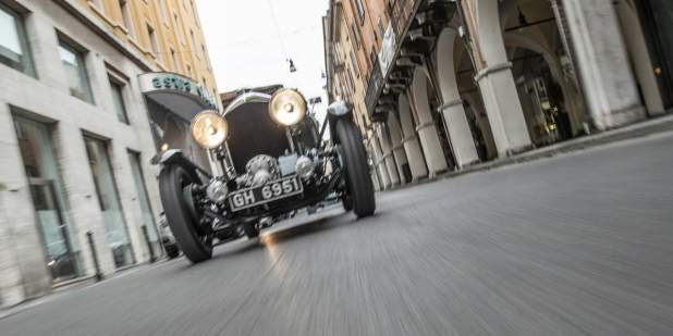 Low front view of a heritage Bentley Blower car driving past buildings | Bentley Motors