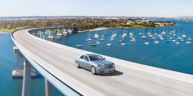 Aerial view of a light blue Bentley Mulsanne driving over a bridge above sea | Bentley Motors