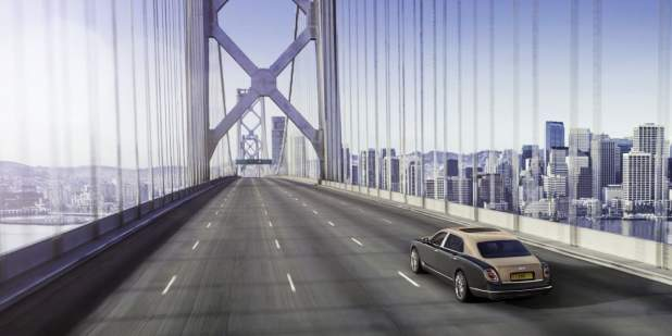 Duo-coloured Bentley Mulsanne Extended Wheelbase driving on a bridge overlooking the city | Bentley Motors