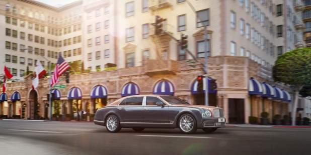 Duo-toned Mulsanne Extended Wheelbase driving past shops and apartment buildings | Bentley Motors