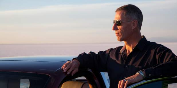 Andy Green wearing sunglasses, leaning over his Bentley and admiring the sunset    Bentley Motors