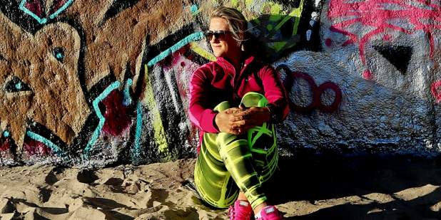 Tennis player Victoria Azarenka, sat on a beach, leaning against a graffiti wall | Bentley Motors