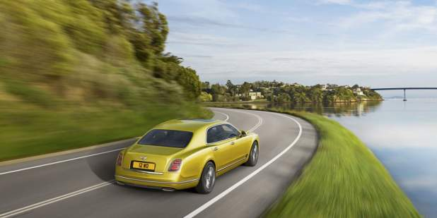 Rear profile of a gold Bentley Mulsanne Speed driving on a lake front | Bentley Motors