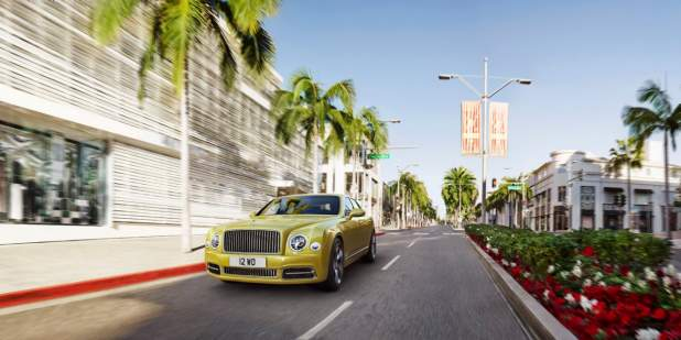 Gold Bentley Mulsanne Speed driving past shops, palm trees and flowers | Bentley Motors