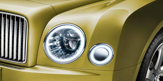 Close up of a gold Bentley Mulsanne LED headlamps with the Bentley logo | Bentley Motors