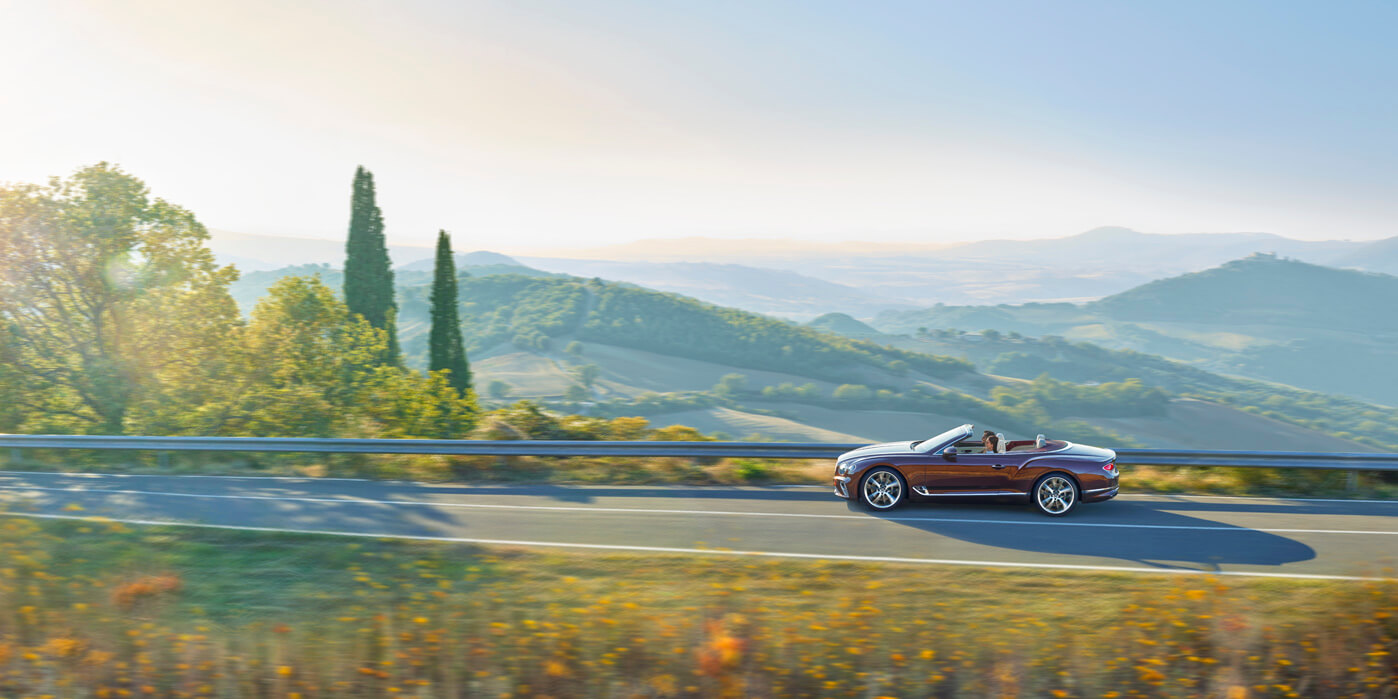 New Continental GT Convertible in Cricket Ball red paint colour driving on mountain road in Italy