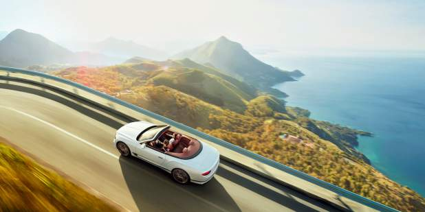 new-Ice-white-Bentley-Continental-GT-Convertible-driving-in-mountains-with-sea-on-right-below