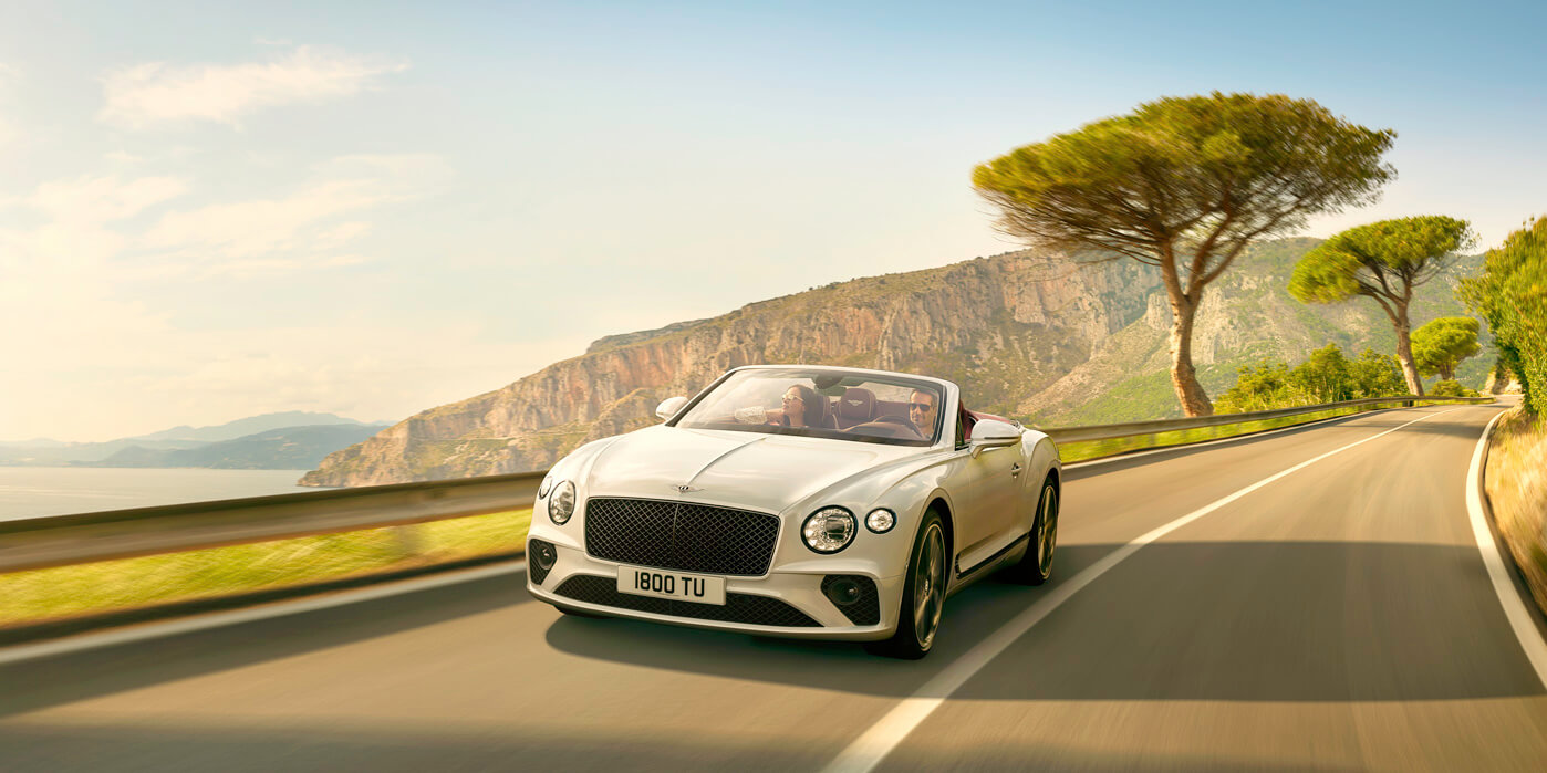 New Continental GT Convertible in Ice white paint colour driving on a high mountain road in Italy by the sea
