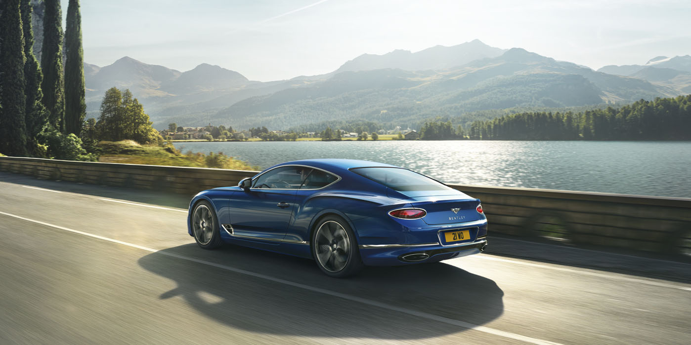 New Continental GT driving by a lake in northern Italy in Sequin Blue paint colour