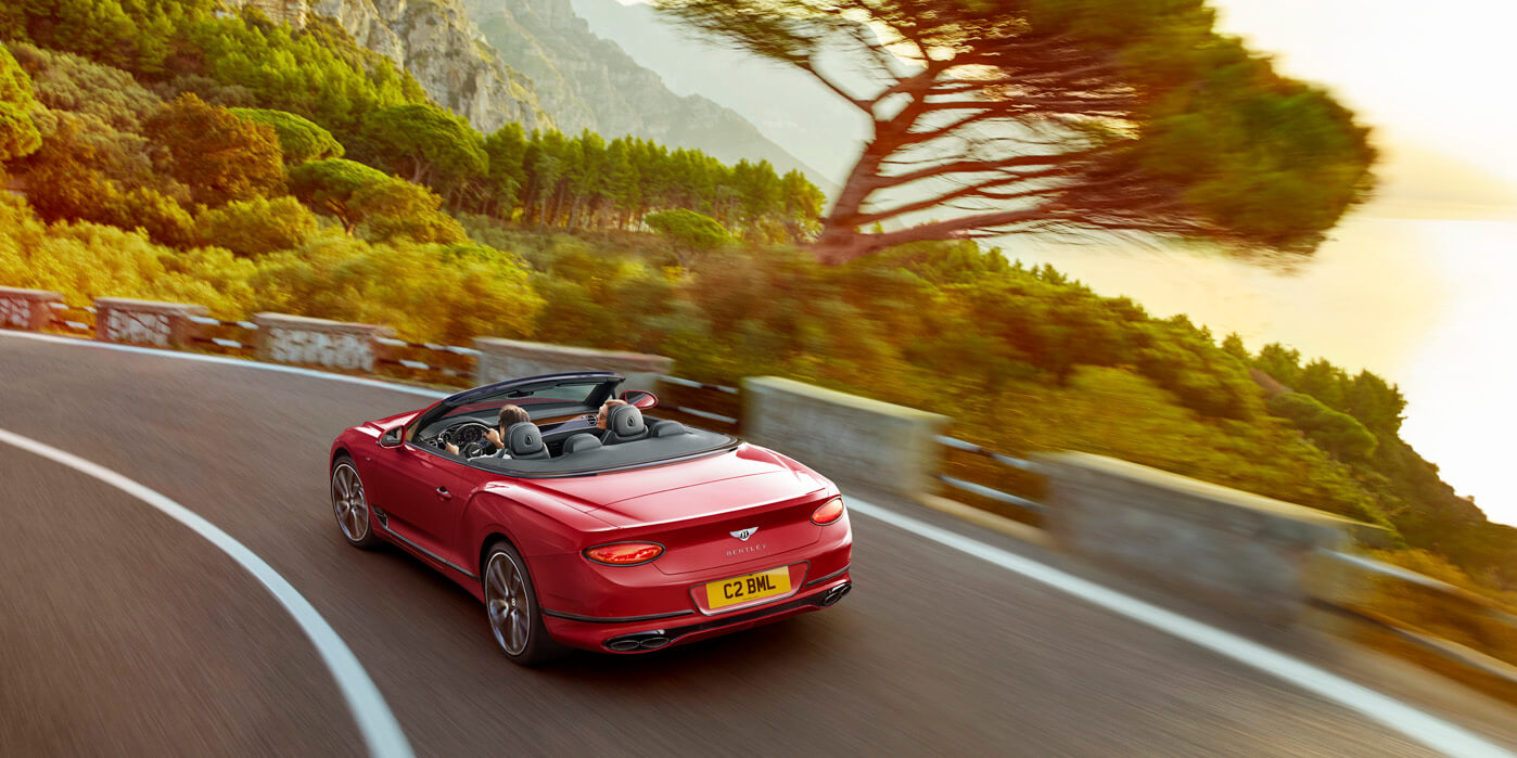 New Continental GT V8 Convertible driving in mountains past sea