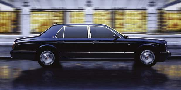 Side view of a black Bentley Arnage RL saloon driving past a building | Bentley Motors
