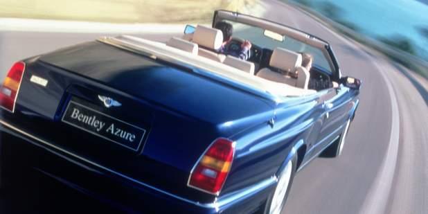 Rear view of a blue Bentley Azure driving on a coastal road | Bentley Motors