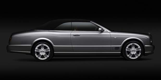 Side of a dark grey Bentley Azure T Convertible with the roof up | Bentley Motors