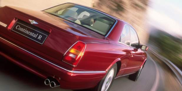 Rear view of a red Bentley Continental R driving on a mountain road   Bentley Motors